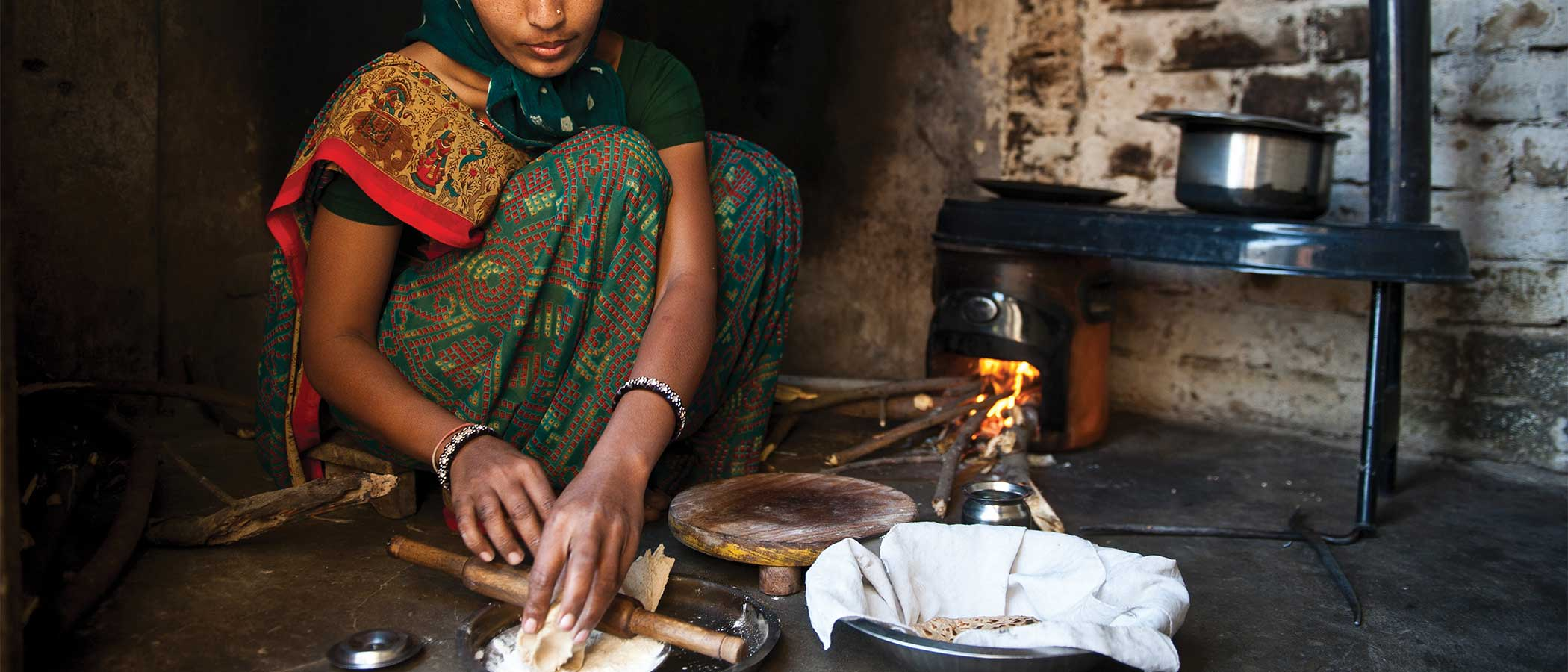 A woman prepares food on an improved cookstove in her home in the Indian state of Gujarat.