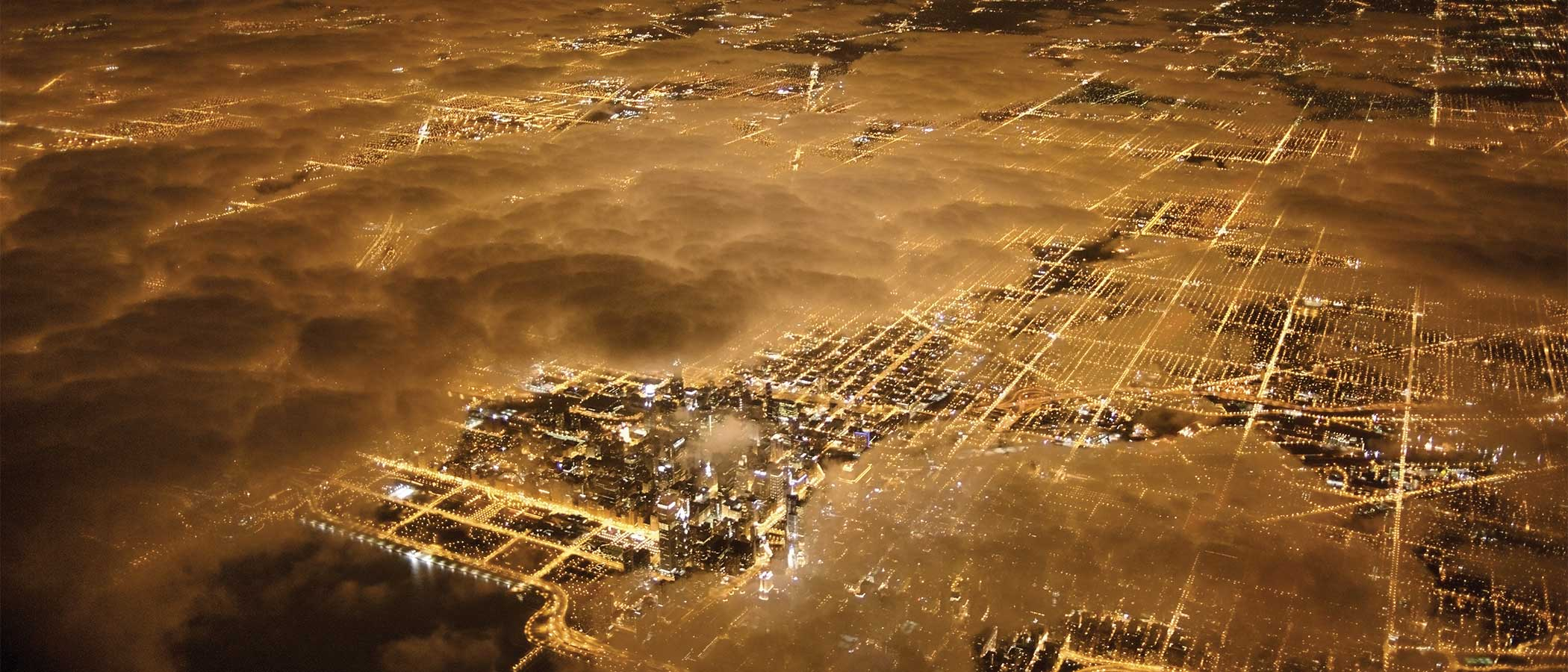 Aerial view of a city at night with glowing lights of buildings and streets.