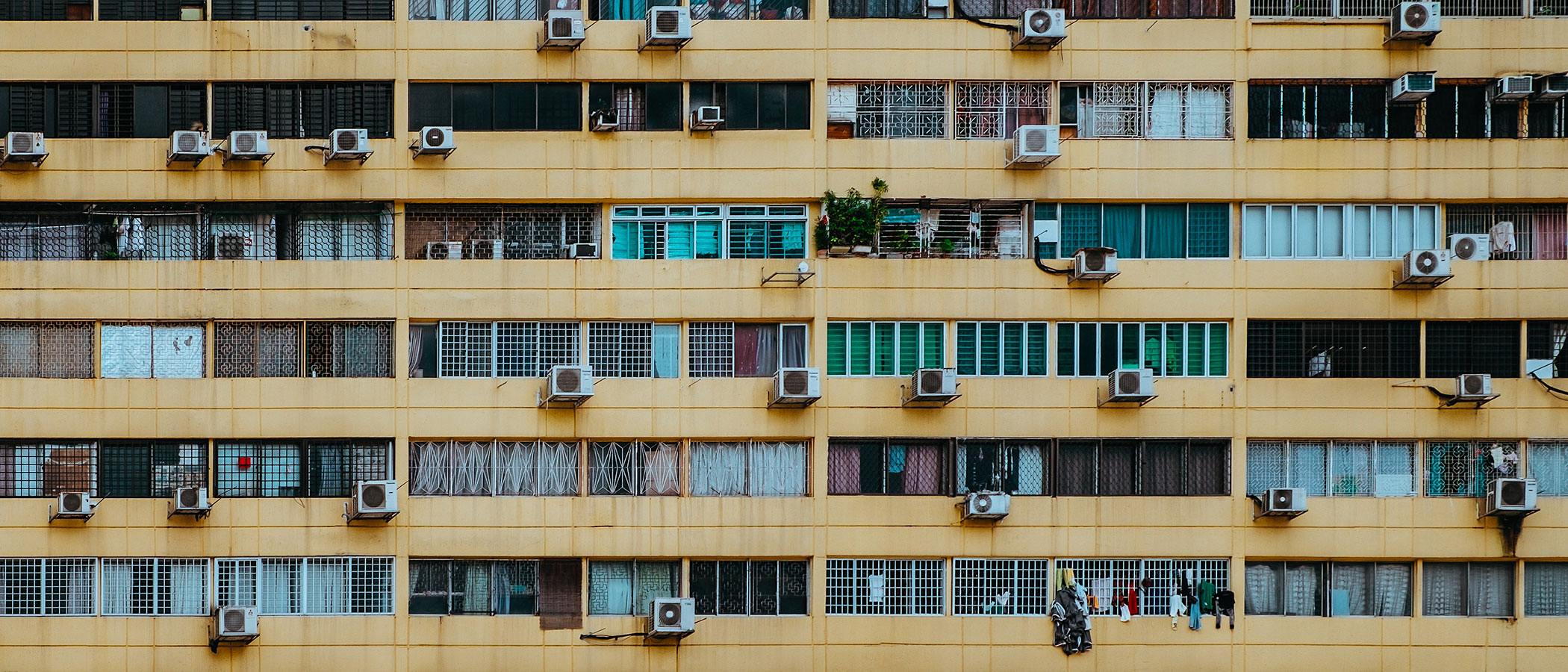 Many air conditioning units on the side of a large apartment building.