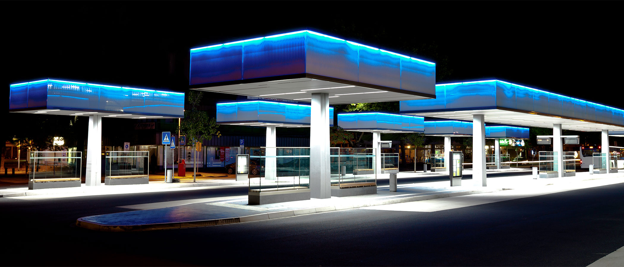 A modern bus terminal lit by blue and white LED lighting under protected canopies.