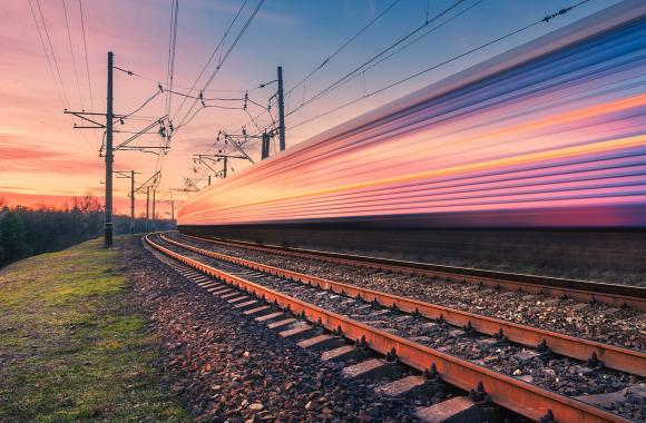 Fast-moving electric train on rural tracks at sunset.